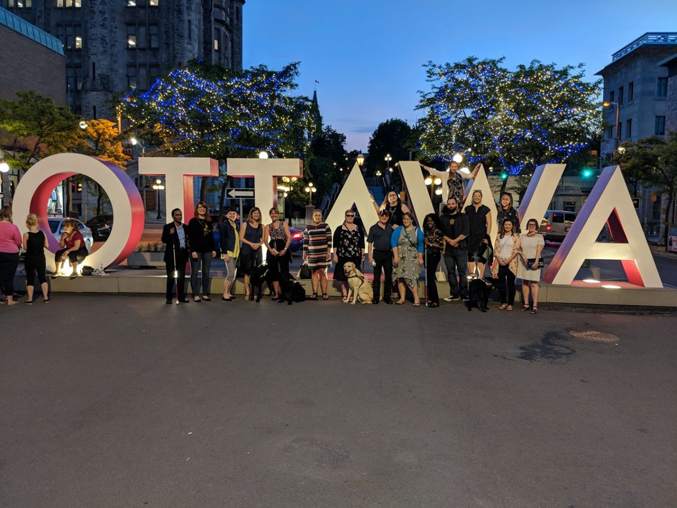 A group of people and guide dogs stand in front of the Ottawa sign.