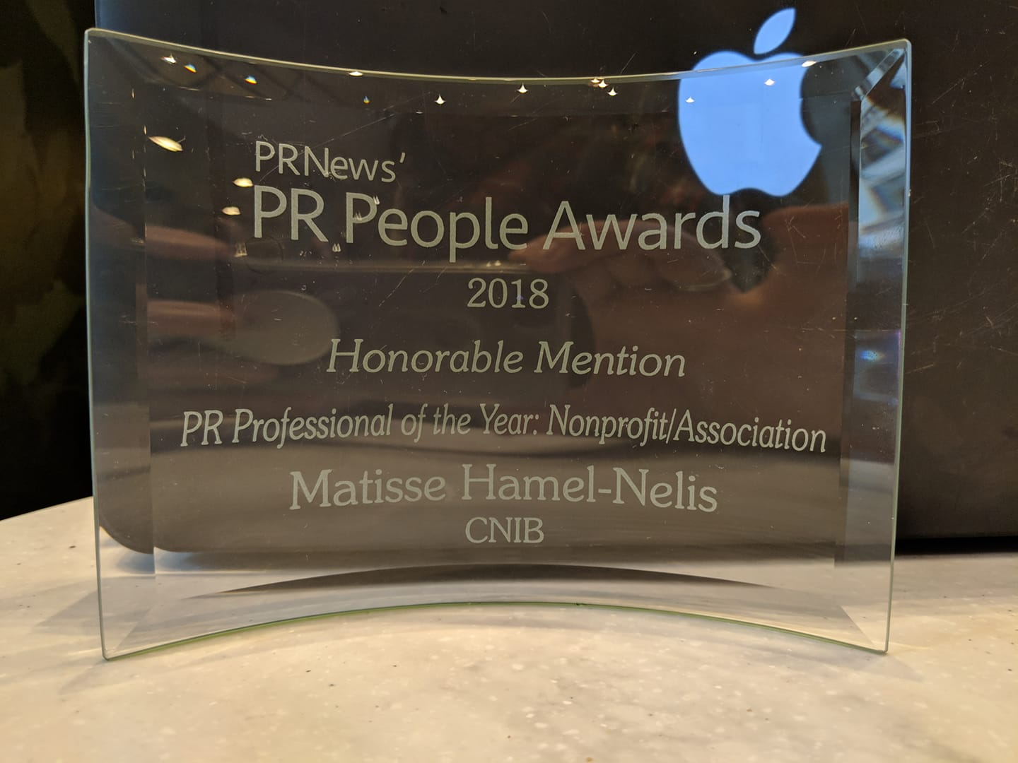 """A curved glass plaque with engraved text: """"PR News' - PR People Awards 2018 - Honourable Mention - PR Professional of the Year: Nonprofit/Association - Matisse Hamel-Nelis - CNIB"""""""