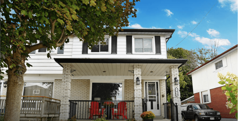 Front of a house with a porch with two red Muskoka chairs.