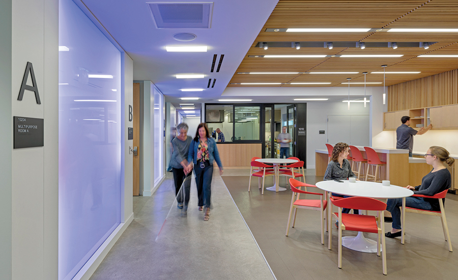 Colour=changing LED panels animate the polished concrete circulation path and an adjacent social space as two women walk by.