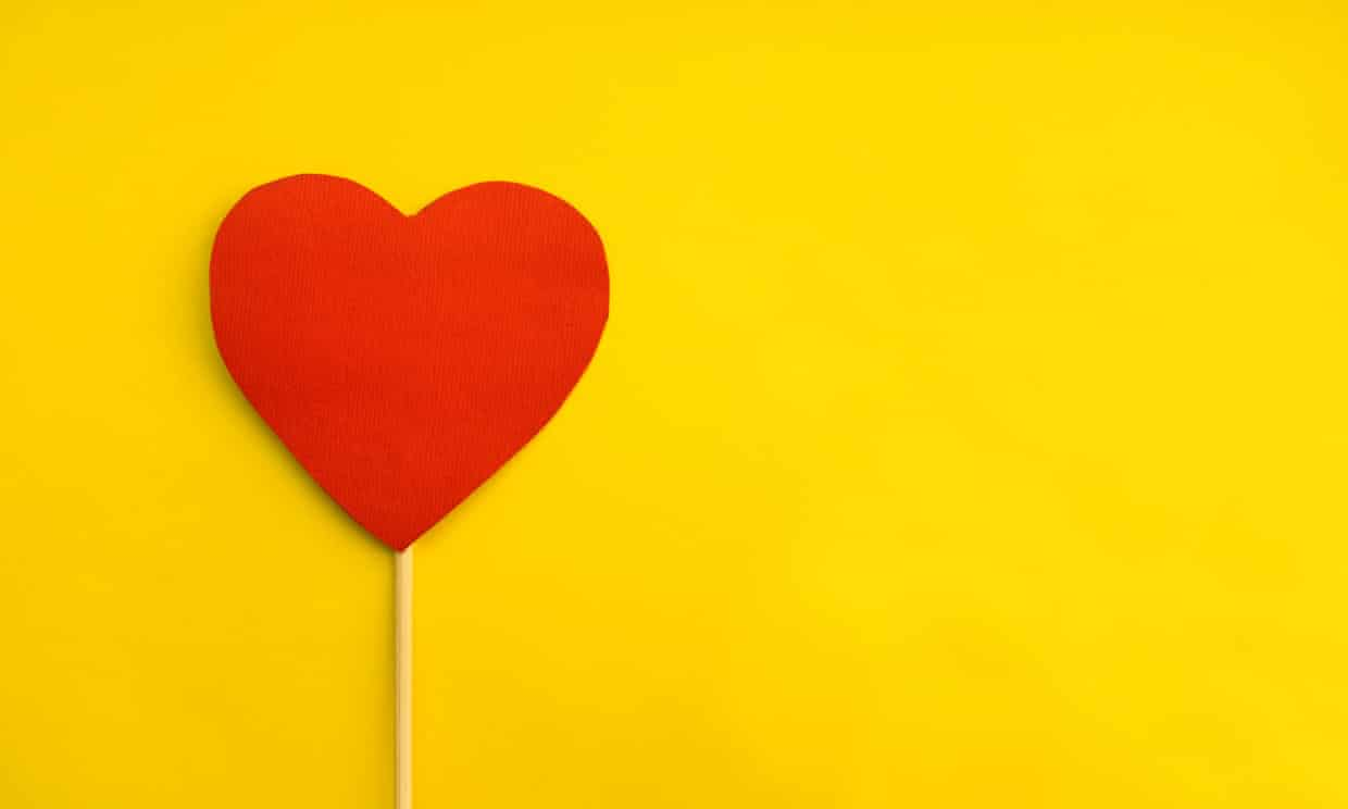 Red heart on a stick on a yellow background