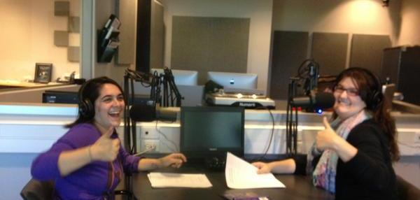 Ali and Mati in a radio booth holding their scripts and giving a thumbs up