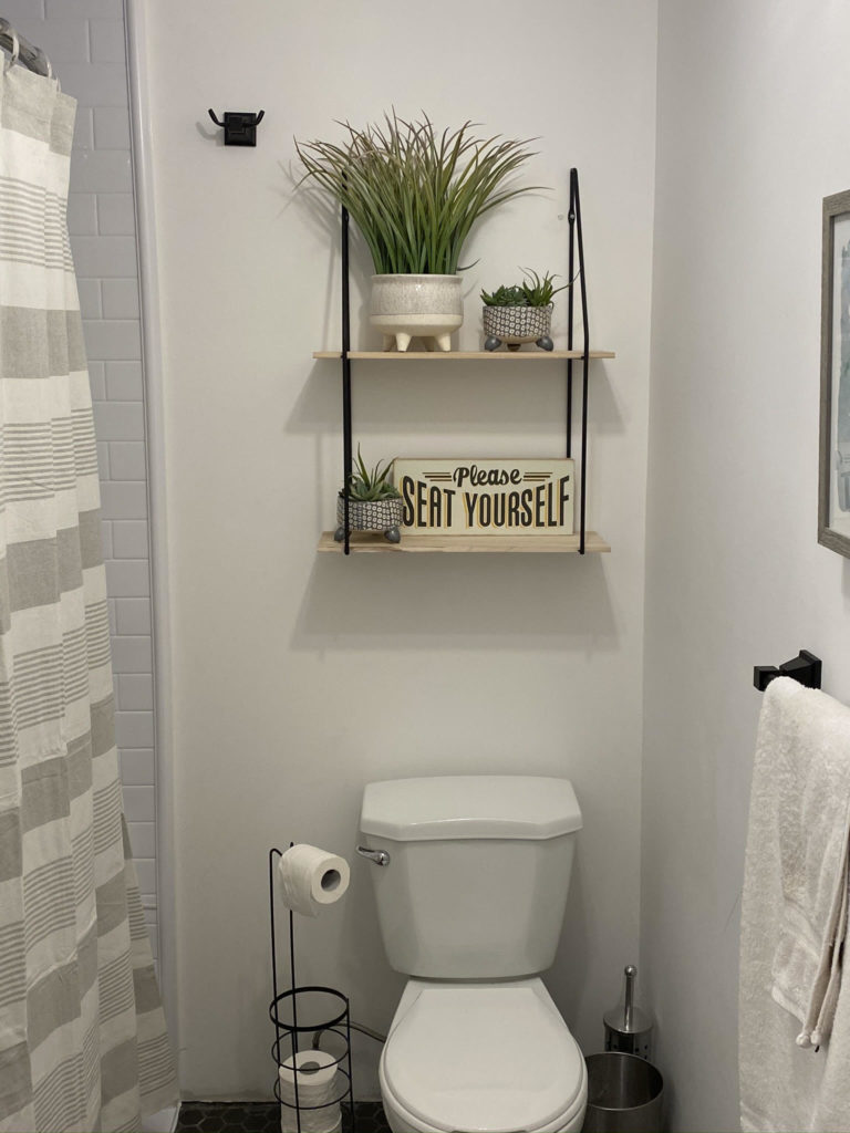 """Toilet with shelvingToilet with a shelving unit above with various green plants and a sign tat reads """"Please seat yourself."""" unit above with various green plants"""
