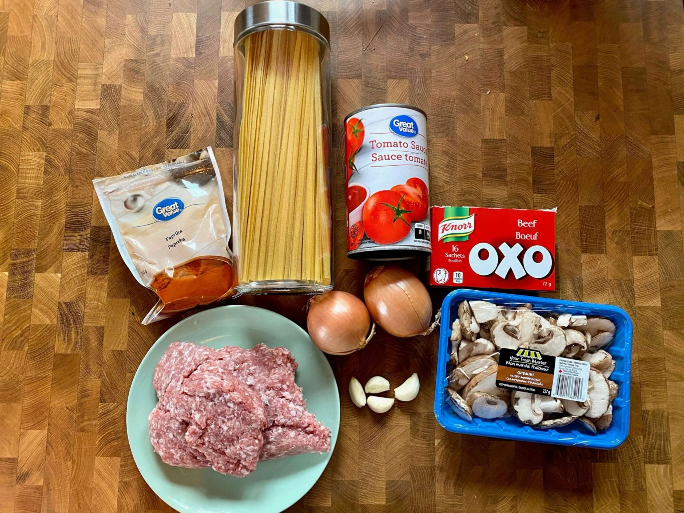 Top view of ground pork on a plate, a bag of paprika, a jar with spaghetti, a can of tomato sauce, two onions, some garlic cloves, a box of beef bouillon, and a package of mushrooms.