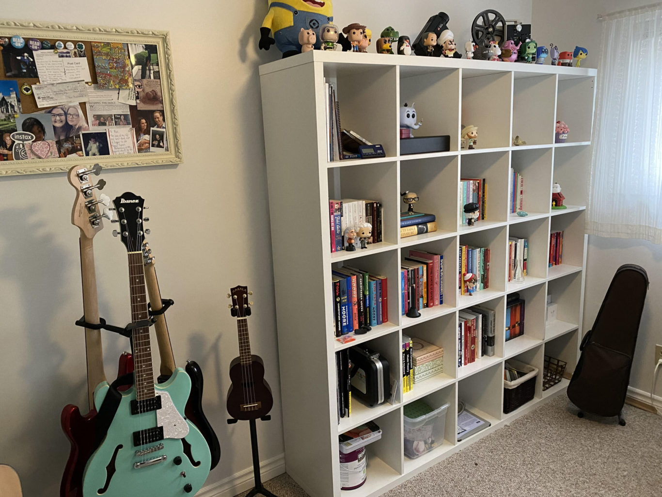 A bunch of electric guitars and a ukulele on stands next to a large shelving unit filled with books and Pop Funkos
